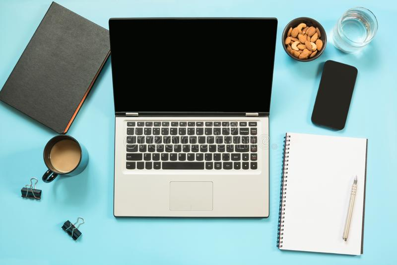 Lugar de trabajo con el ordenador portátil abierto, accesorio en la tabla del azul de la oficina Espacio de la visión superior y  foto de archivo libre de regalías