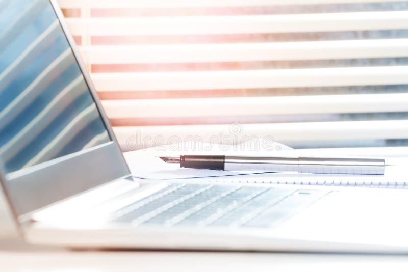Lugar de trabajo con el ordenador portátil abierto y pluma en el escritorio foto de archivo