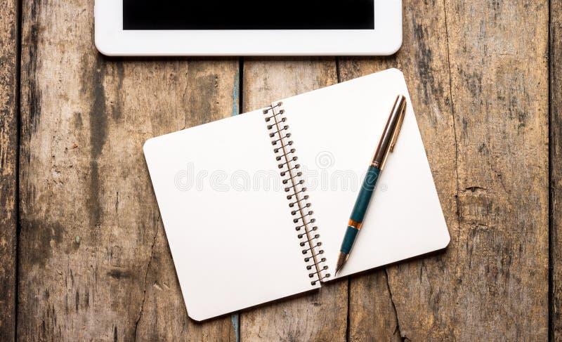 Lugar de trabajo con la tableta digital en fondo de madera fotografía de archivo libre de regalías