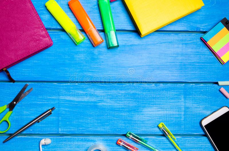 Lugar de trabajo del alumno de la escuela en una tabla de madera azul Desorden creativo, plumas dispersadas y lápices Lugar para  fotos de archivo libres de regalías