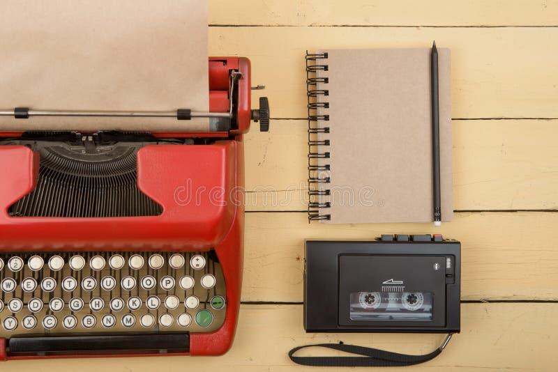 Lugar de trabajo del escritor o del periodista - m?quina de escribir roja del vintage en el escritorio de madera amarillo fotos de archivo libres de regalías