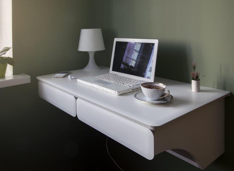 Lugar de trabajo escandinavo del estilo - tabla colgante blanca, ordenador portátil blanco y lámpara de lectura fotos de archivo