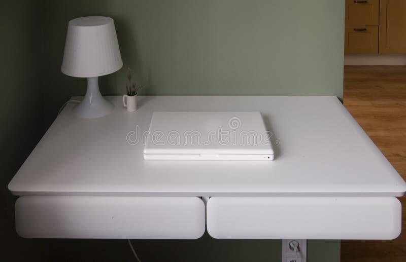 Lugar de trabajo escandinavo del estilo - tabla colgante blanca, ordenador portátil blanco y lámpara de lectura imagenes de archivo