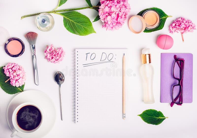 Lugar de trabajo femenino de la visión superior con para hacer la lista, los accesorios cosméticos, la taza de café, el cuaderno, foto de archivo