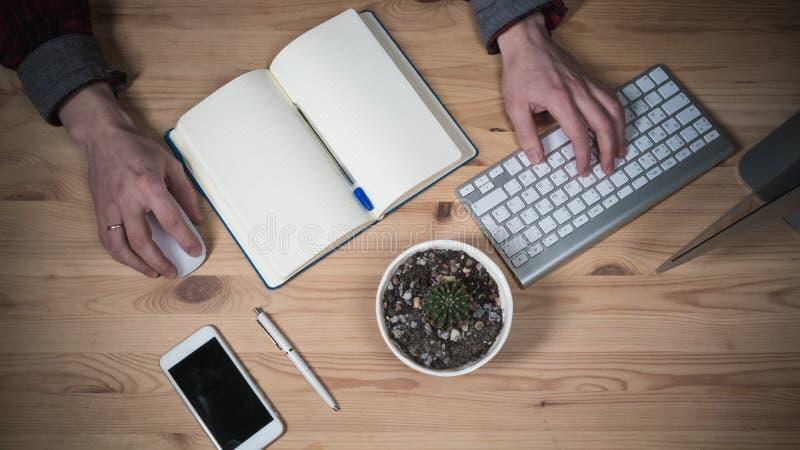 Lugar de trabajo de la oficina con las manos Ordenador portátil, planificador diario, vidrios y teléfono en una tabla de madera V foto de archivo libre de regalías