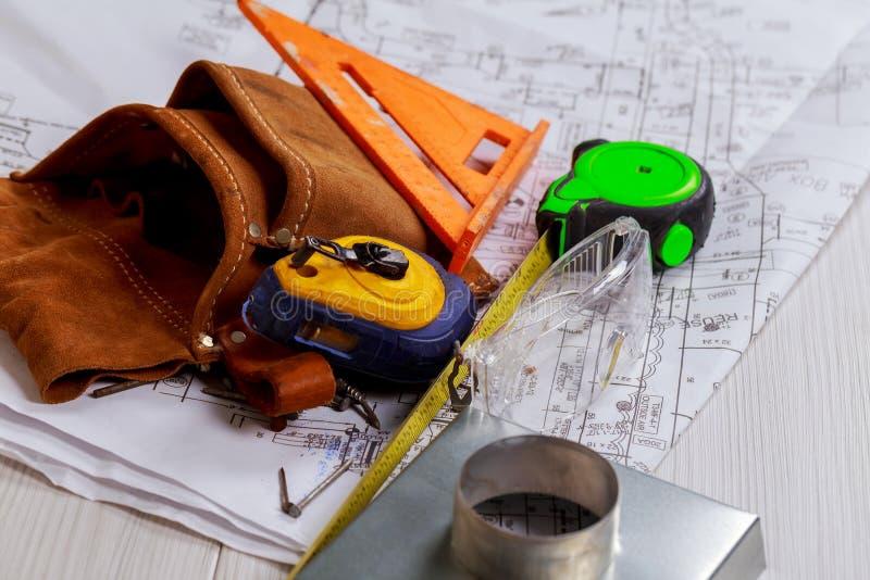 Lugar de trabajo de los equipos del trabajador cuchillo de papel y cinta métrica Diseño de la construcción Planes de papel de la  fotos de archivo libres de regalías