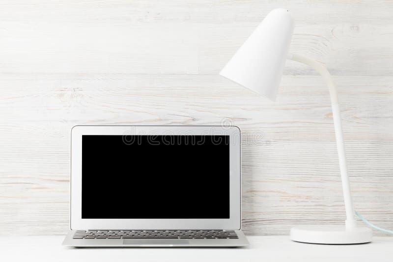 Lugar de trabajo de Ministerio del Interior con el ordenador port?til de la pantalla en blanco fotografía de archivo libre de regalías