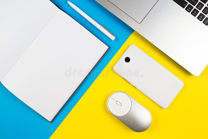 Lugar de trabajo moderno con el cuaderno, el ratón del ordenador, el teléfono móvil y la pluma blanca en fondo azul y amarillo de fotografía de archivo