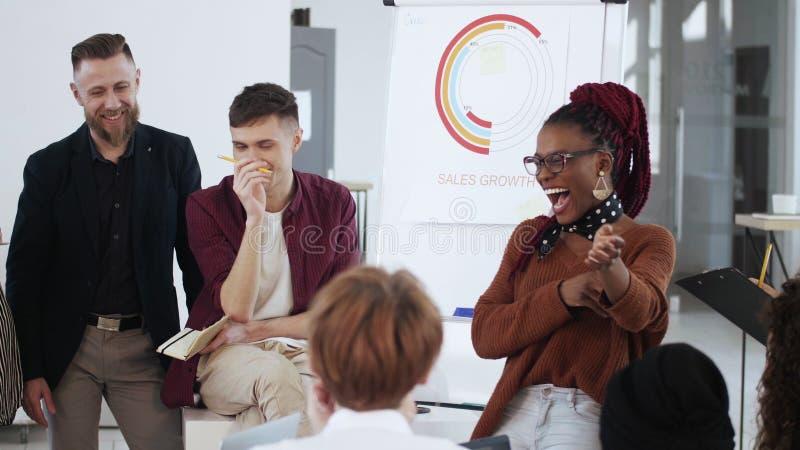 Lugar de trabajo saludable, joven sonriente joven jefa de negocios africana dando instrucciones a diversos empleados de oficina fotografía de archivo libre de regalías