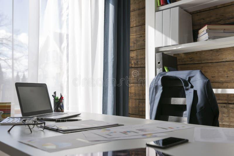 Lugar de trabajo vacío con el escritorio de oficina y silla, chaqueta en la silla, fotografía de archivo