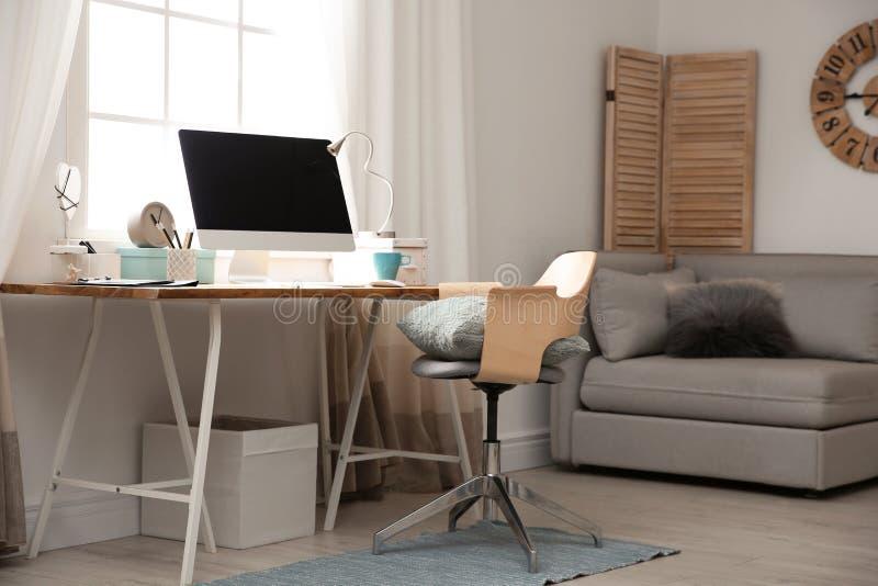 Lugar de trabalho claro com o computador perto da janela em casa interior imagem de stock