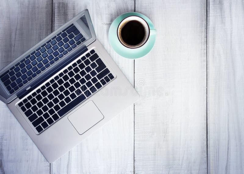 Lugar de trabalho do copo de café do portátil no espaço vazio do fundo de madeira foto de stock royalty free