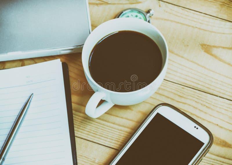 Lugar de trabalho do negócio com smartphone da xícara de café, pena, caderno, fotografia de stock royalty free
