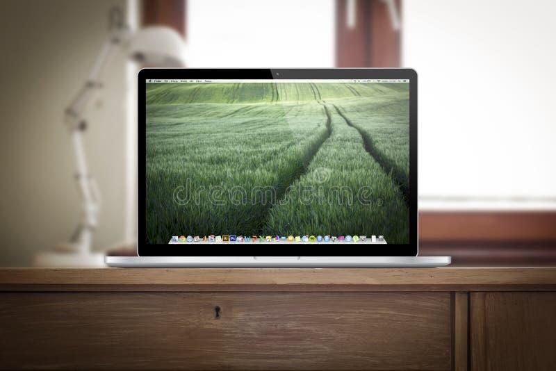 Lugar del trabajo con la favorable retina del macbook en el escritorio imágenes de archivo libres de regalías
