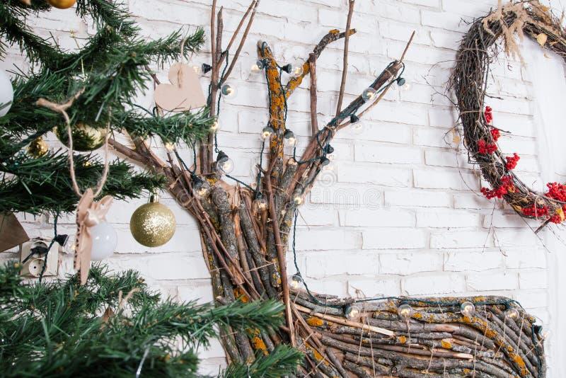 Lugar do ` s do ano novo no estúdio com um cervo, decorado com uma árvore de Natal, presentes, uma cesta dos cones foto de stock royalty free