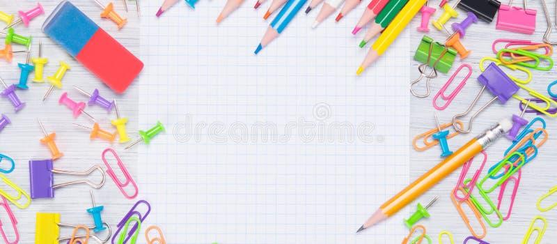 lugar a escrever, cercado pelos suportes coloridos, por lápis coloridos e por clipes de papel fotografia de stock