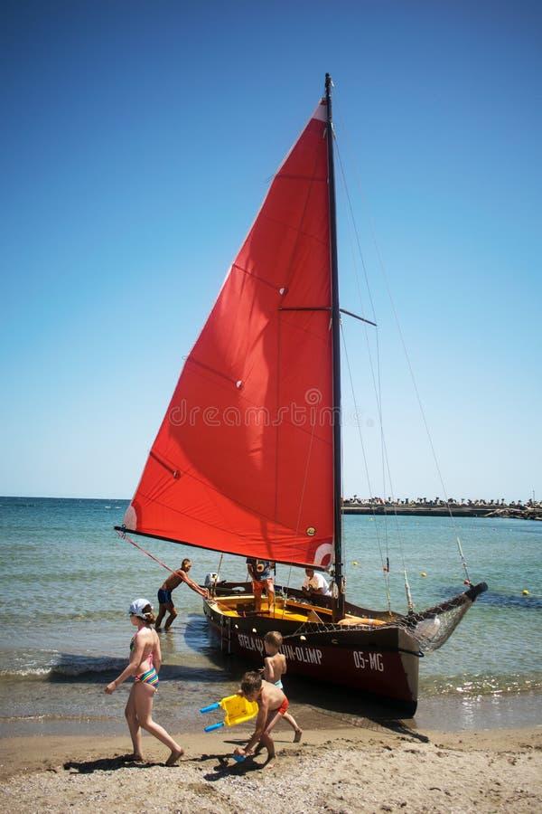 Lugar: Europa, Romênia, recurso do Júpiter Data: julho, 07, 2019 O veleiro vermelho no litoral está esperando para transportar o  foto de stock royalty free