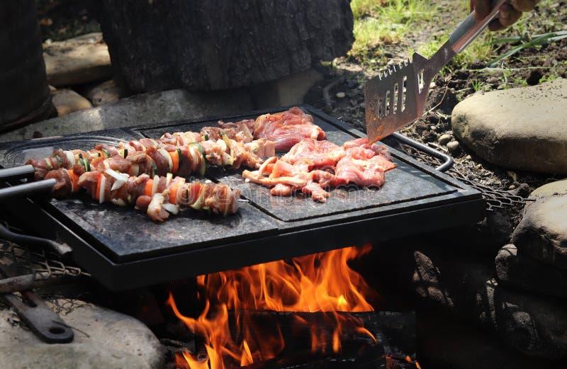 Lugar maravilhoso Anel pequeno do fogo com a chama alaranjada bonita Mesa especial feita do granito Fritada da carne da galinha e imagem de stock