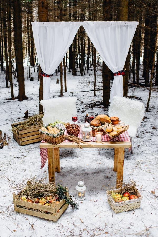 Lugar na madeira de pinho do inverno decorada para um piquenique romântico fotos de stock royalty free