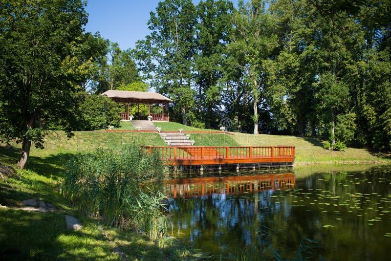 Lugar para la ceremonia - paisaje hermoso con una charca y un gazebo imagen de archivo