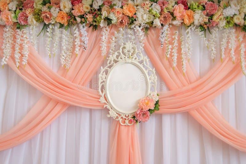 Lugar para os recém-casados decorados com flores e pano do pêssego com um quadro vazio do casamento para nomes dos noivos fotografia de stock royalty free