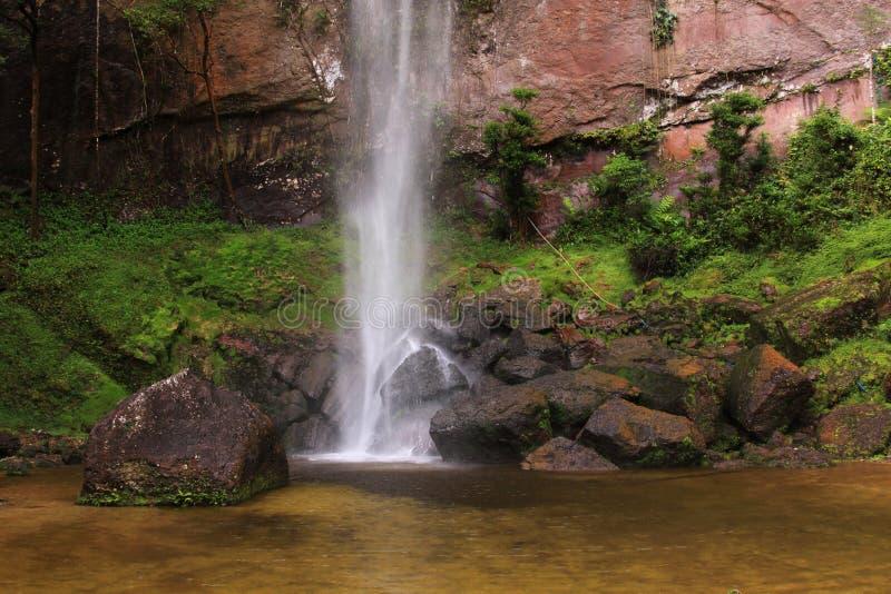 Lugar relajante cerca de la cascada y de la pared de piedra natural imagen de archivo