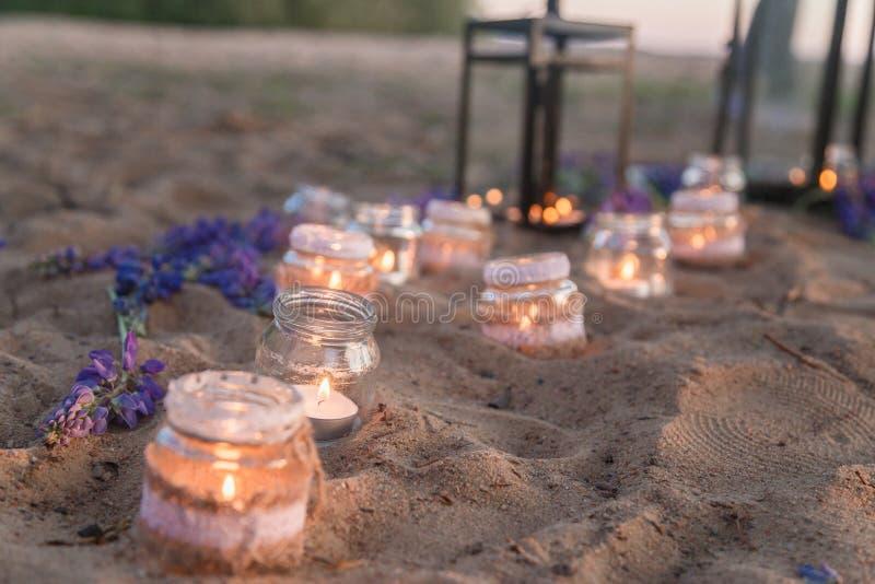 Lugar romántico adornado hermoso por una fecha con los tarros llenos de velas que cuelgan en árbol y la situación en una arena imagen de archivo