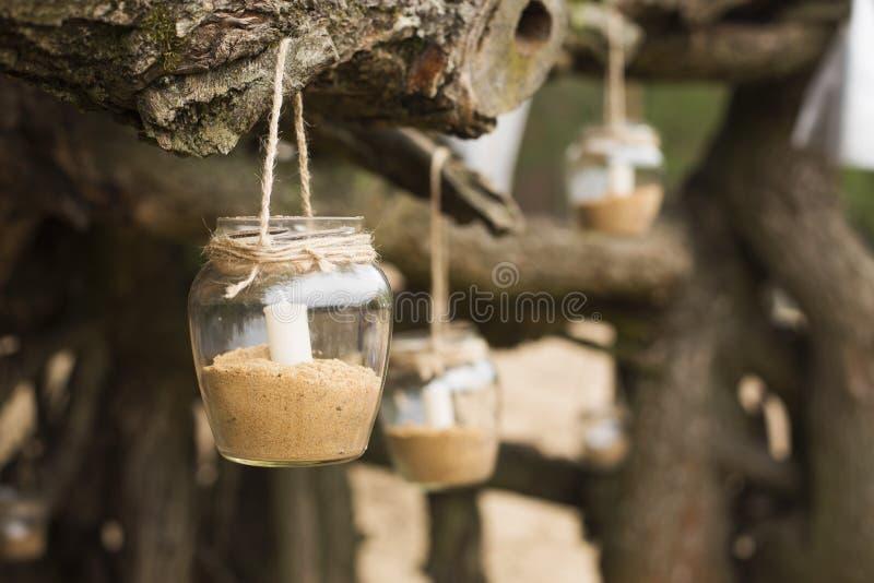 lugar romântico decorado por uma data com os frascos completos das velas que hunging na árvore Copie o espaço imagem de stock royalty free