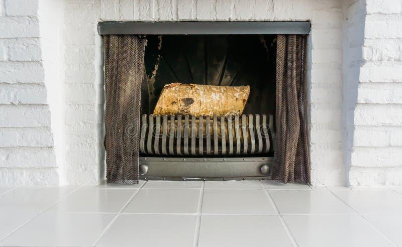 Lugar Unlit do fogo com arquitetura branca e logs não de queimadura dentro do fundo imagem de stock