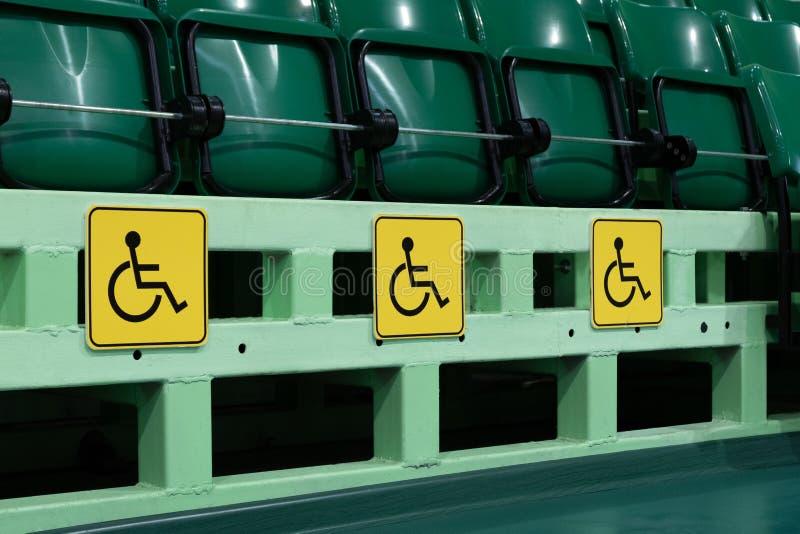 Lugares para discapacitado en el auditorio Asientos verdes en un estadio o en un complejo de los deportes concepto de proteger la imagen de archivo