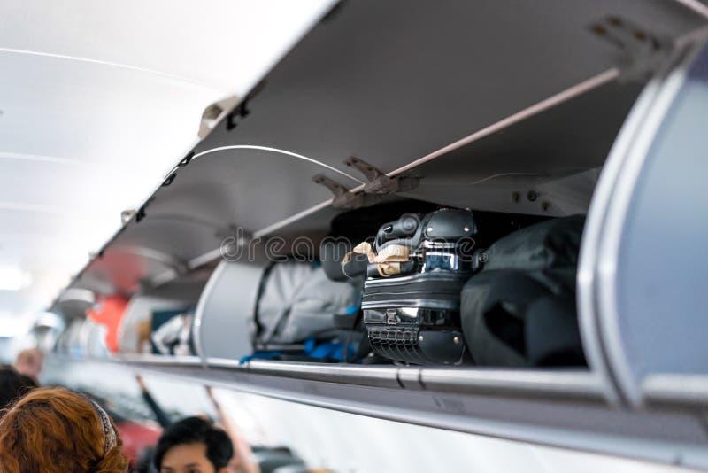 Luggage on airplane shelf overhead passenger seat stock image