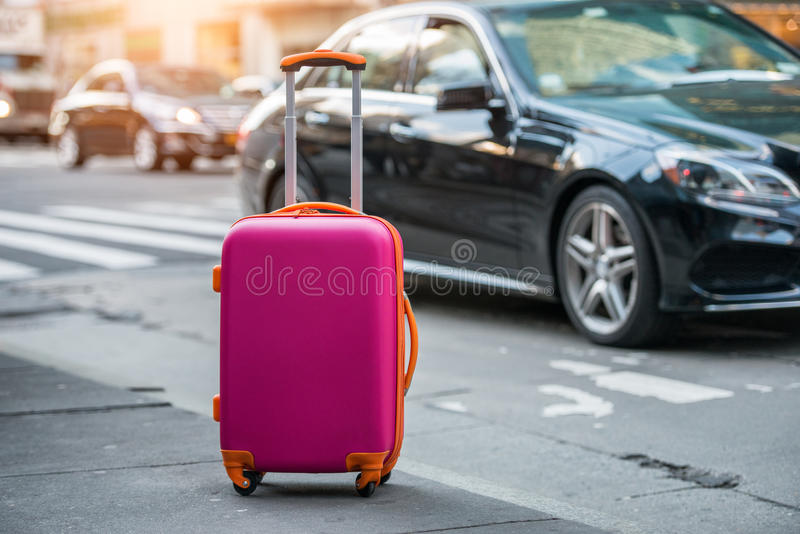 Luggage bag on the city street ready to pick by airport transfer taxi car. royalty free stock image