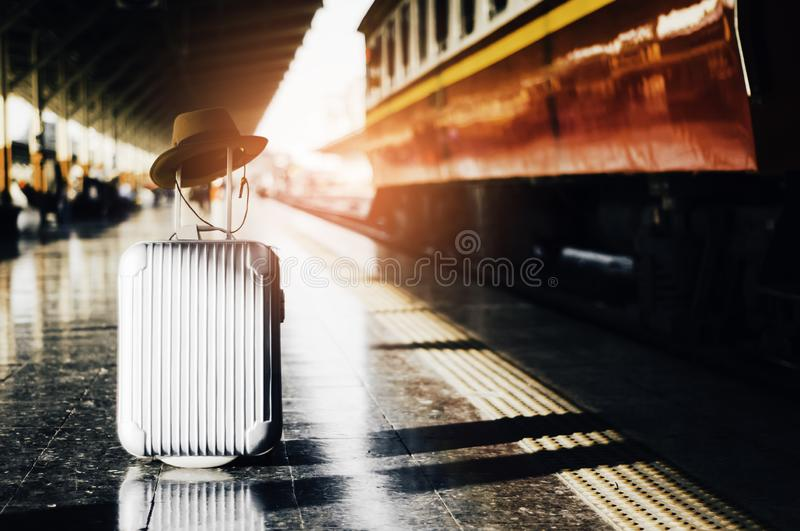 Luggage and hat are placed on platform in the train station, wh. Ile awaiting trains with abstract concepts, learning and travel to a wide world of travelers royalty free stock image