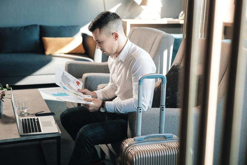 Dark-haired manager having business trip sitting with luggage in hotel royalty free stock images