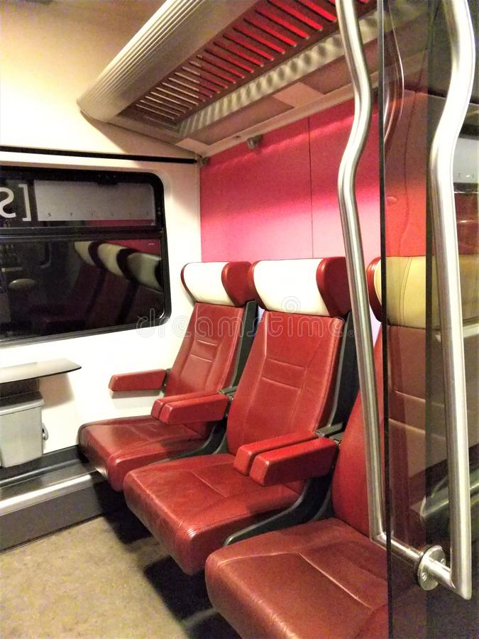 Red pleather seats aboard European train car stock photos