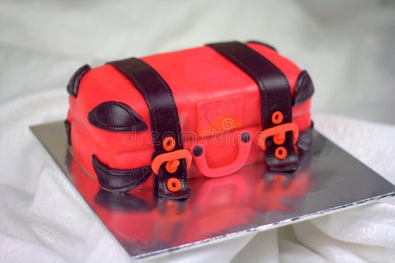 Luggage shaped fondant cake red and black. Luggage shaped fondant cake with red and black color. Bon Voyage theme, farewell cake royalty free stock image