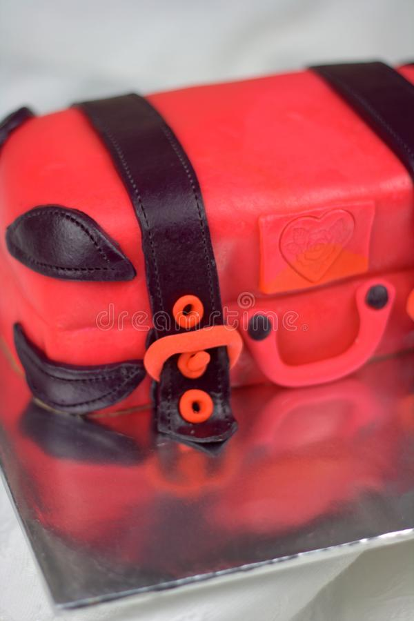 Luggage shaped fondant cake red and black. Luggage shaped fondant cake with red and black color. Bon Voyage theme, farewell cake royalty free stock photography