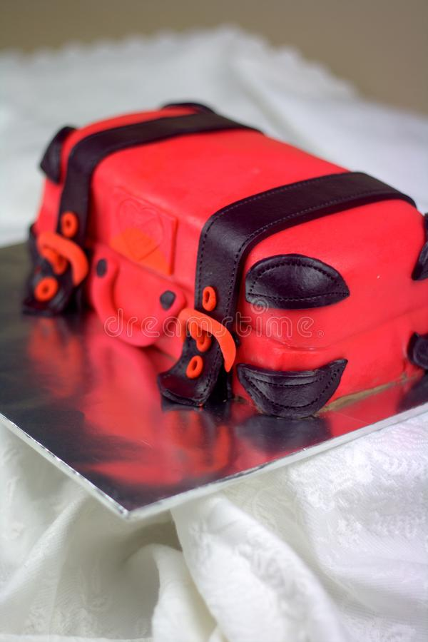 Luggage shaped fondant cake red and black. Luggage shaped fondant cake with red and black color. Bon Voyage theme, farewell cake royalty free stock photos