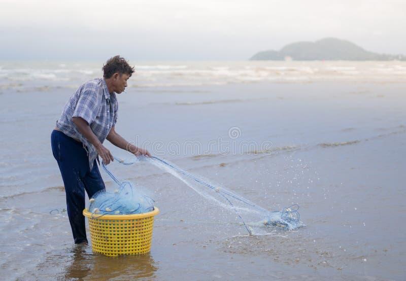 12 luglio 2017 - Chantaburi, pescatore della Tailandia reparing la rete da pesca immagine stock libera da diritti