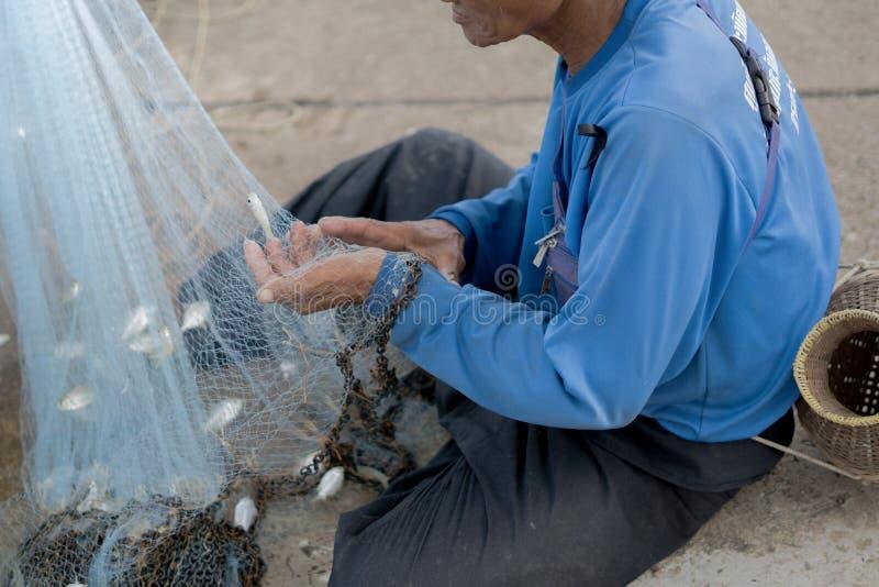 12 luglio 2017 - Chantaburi, Tailandia - pescatori anziani che rimuovono pesce fotografie stock libere da diritti