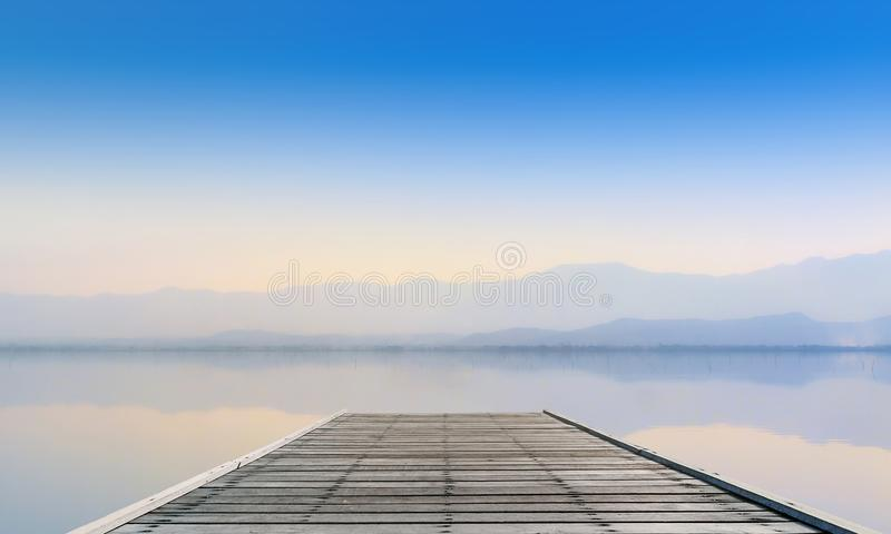 Lugn sjö med berget i solnedgång arkivbilder