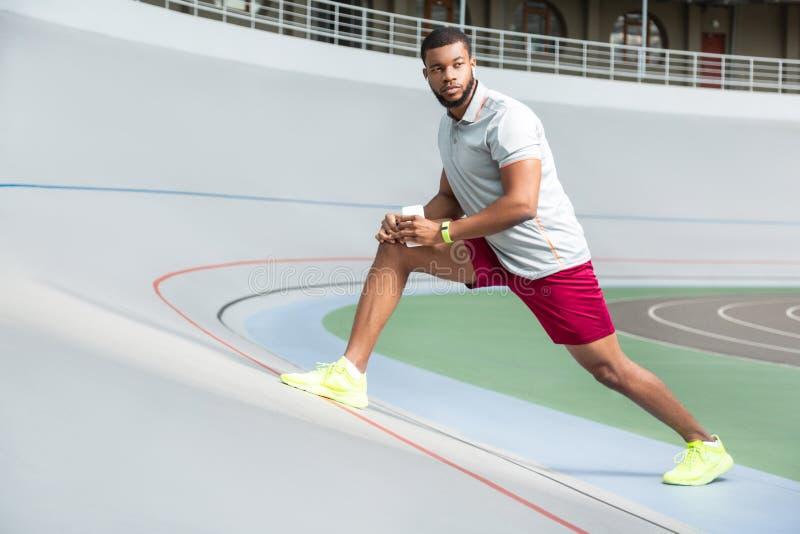 Lugna attraktiv ung man i sportswearen som sträcker muskler fotografering för bildbyråer