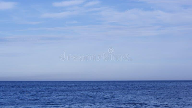 Lugna bl?tt hav och himmel p? en varm sommarafton royaltyfri fotografi