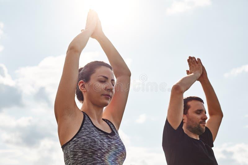 Lugna din mening Närbild av unga par som utomhus mediterar, medan sitta med stängda ögon mot solig himmel arkivbild