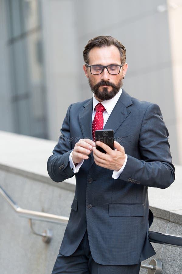 Lugna elegant man som ser skärmen av hans smartphone, medan vara bara royaltyfri bild