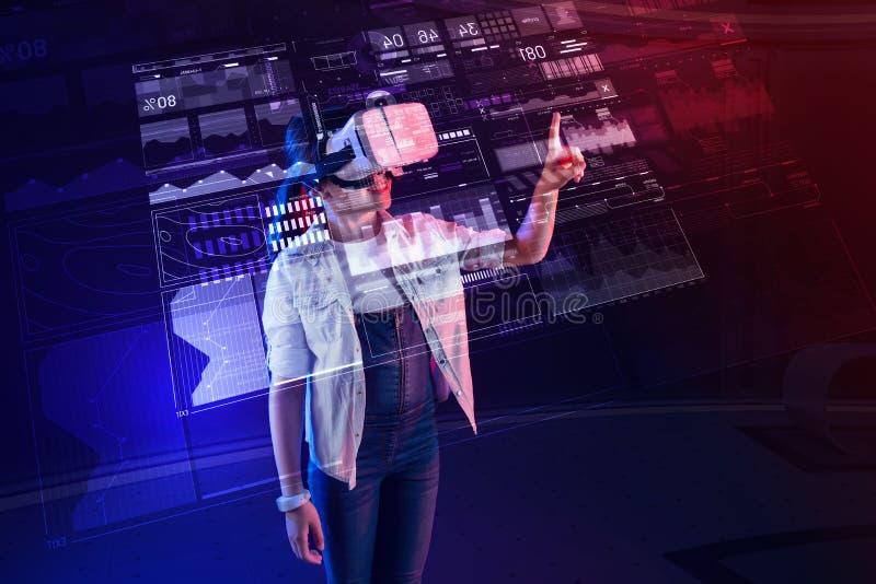 Lugna flicka som trycker på hologrammet och bär virtuell verklighetexponeringsglas arkivbild