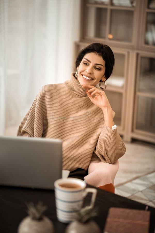 Lugna fridsam attraktiv kvinna som spenderar tid med hennes bärbar dator arkivbilder