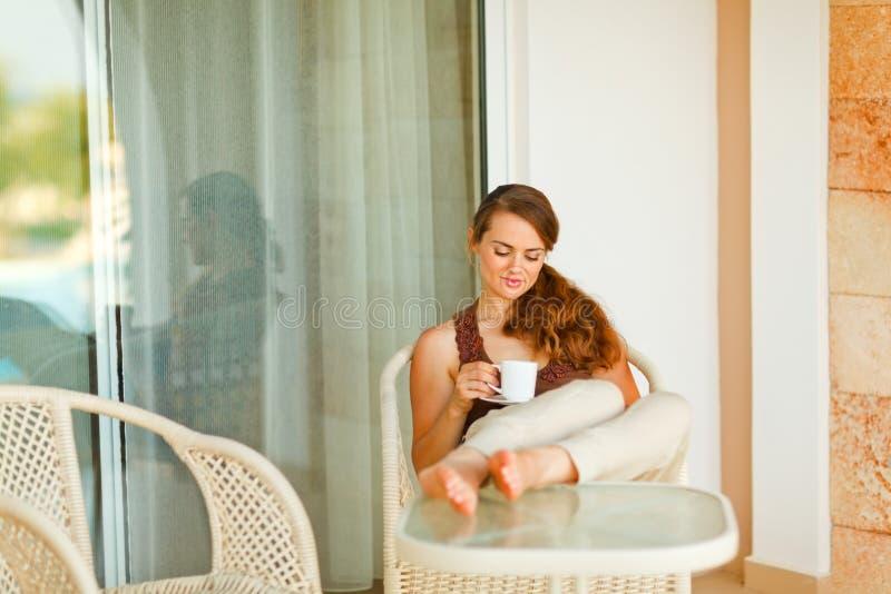 Lugna härlig kvinna som kopplar av på terrass royaltyfri foto