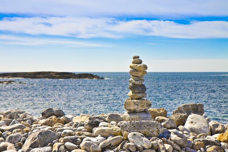 Lugna hav med zenstenar mot ett naturligt landskap - bildintelligens royaltyfria bilder