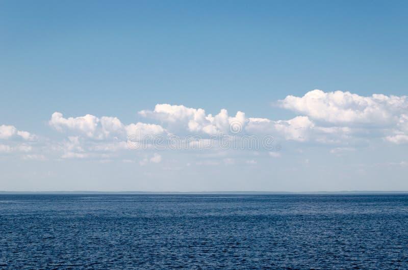 Lugna hav på en bakgrund av blå himmel med cloudsCalmhavet mot blå himmel med moln Harmoni av havsbeståndsdelar seascape kopia royaltyfri foto